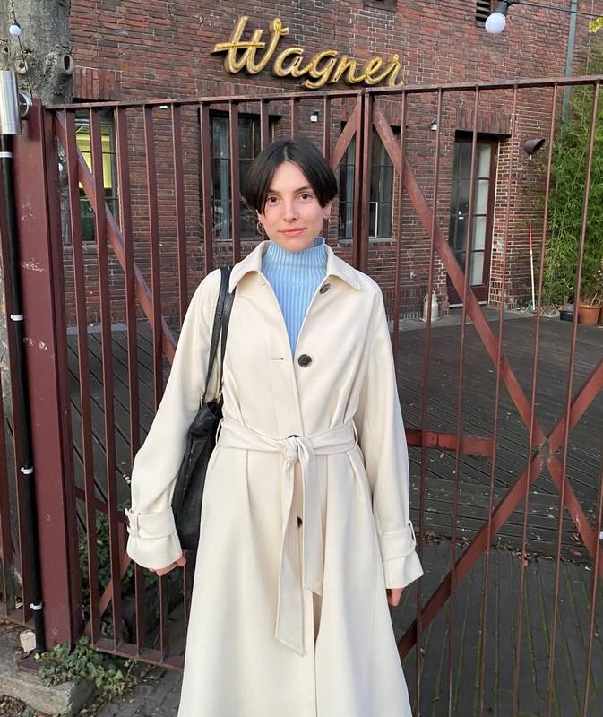 Rosa Wagner steht vor einem Tor aus Metall. In der Hintergrund ein Gebäude mit der Aufschrift Wagner.